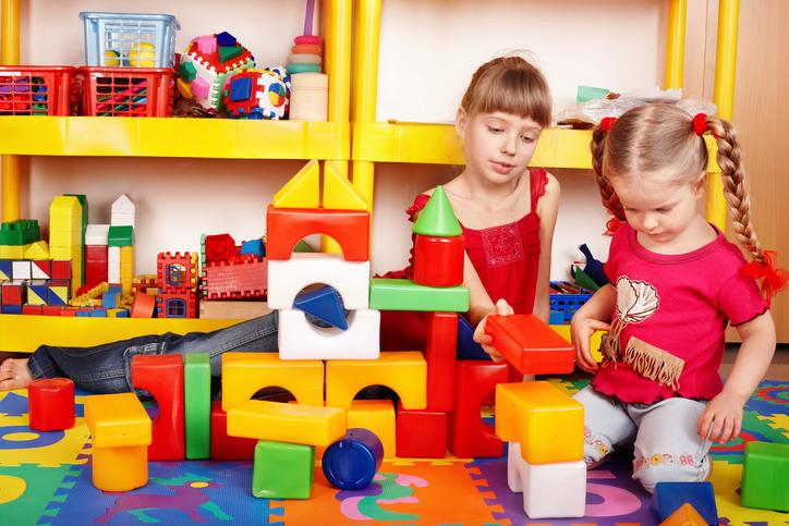 Children  with  block in play room. Preschool.